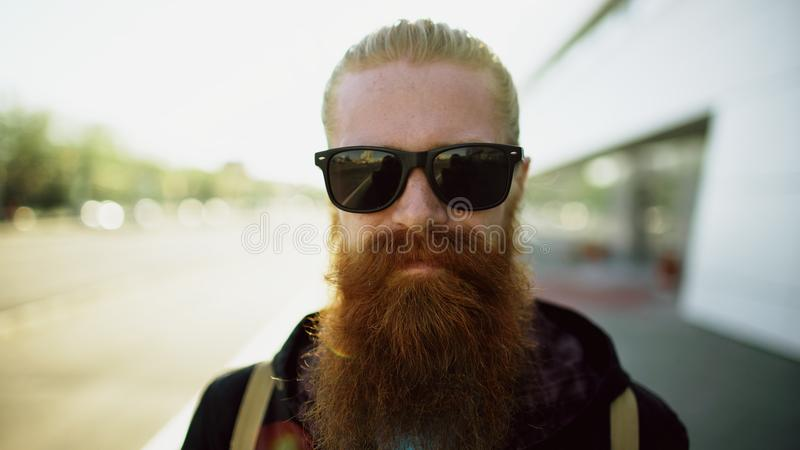 Retrato del primer del hombre barbudo joven del inconformista en gafas de sol que sonríe y que presenta mientras que calle de la  imágenes de archivo libres de regalías