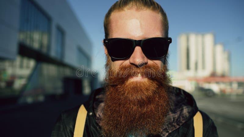 Retrato del primer del hombre barbudo joven del inconformista en gafas de sol que sonríe y que presenta mientras que calle de la  foto de archivo