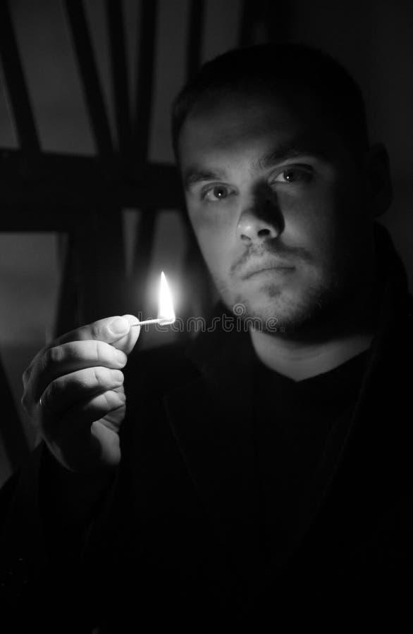 Retrato del primer del hombre caucásico serio o peligroso joven atractivo con el partido ardiendo en su mano Fondo negro fotos de archivo