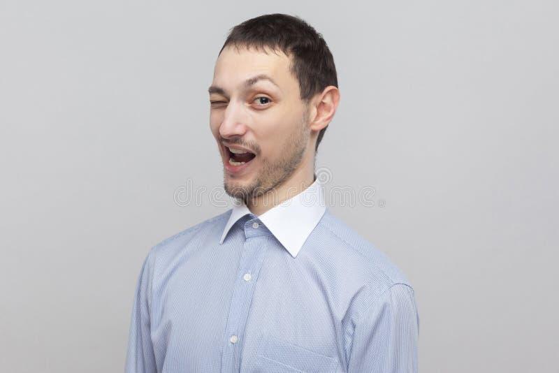 Retrato del primer del hombre de negocios hermoso divertido de la cerda en la camisa azul clara clásica que coloca, guiñando y mi imagen de archivo libre de regalías