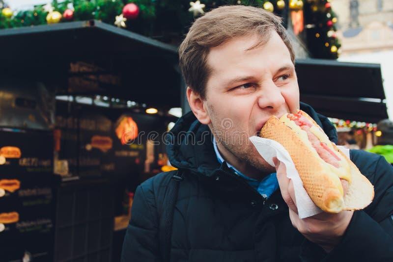 Retrato del primer del hombre hambriento en vidrios que come el perrito caliente en el fondo del aire libre fotos de archivo
