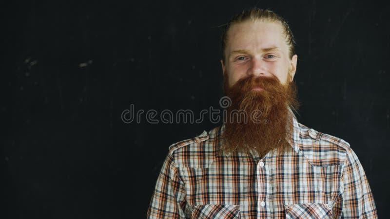 Retrato del primer del hombre del inconformista que mira la cámara y que sonríe en fondo negro imagen de archivo