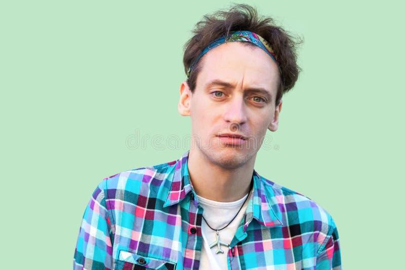 Retrato del primer del hombre joven cansado triste en la situación a cuadros azul casual de la camisa y de la venda y la mirada d imagen de archivo