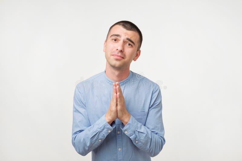 Retrato del primer del hombre joven desesperado en manos abrochadas demostración azul de la camisa, pidiendo ayuda o excusa fotografía de archivo libre de regalías
