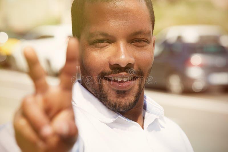 Retrato del primer del inconformista afroamericano joven confiado del hombre en la camisa blanca que muestra el símbolo V de los  fotos de archivo libres de regalías