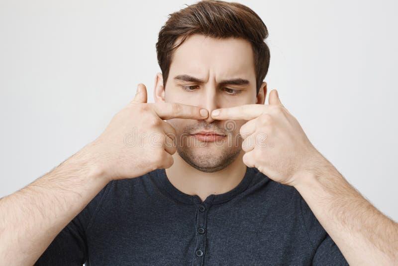 Retrato del primer del individuo divertido con el corte de pelo lindo que toca su nariz con ambos dedos índices y que la mira, co foto de archivo