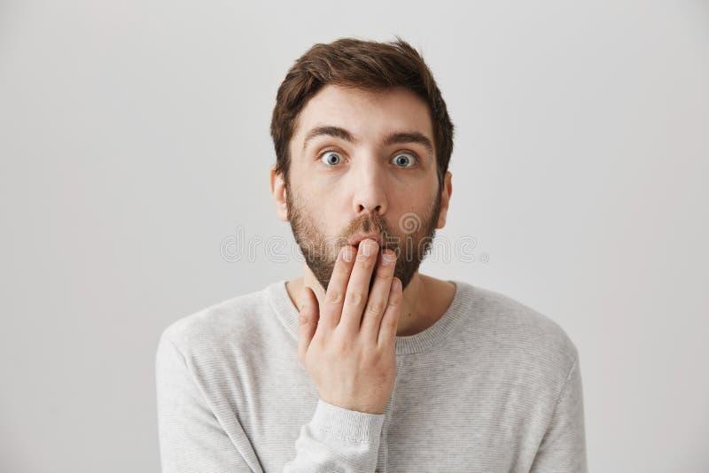 Retrato del primer del individuo joven sorprendente y chocado con la barba, cubriendo la boca con la palma y mirando fijamente la imagenes de archivo