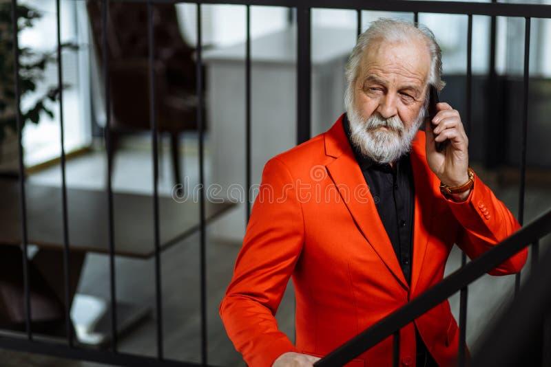 Retrato del primer del jefe mayor que habla en el teléfono y la situación en la escalera foto de archivo