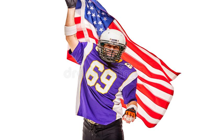 Retrato del primer del jugador de fútbol americano Jugador de fútbol americano con una bandera americana en sus manos Concepto fotos de archivo