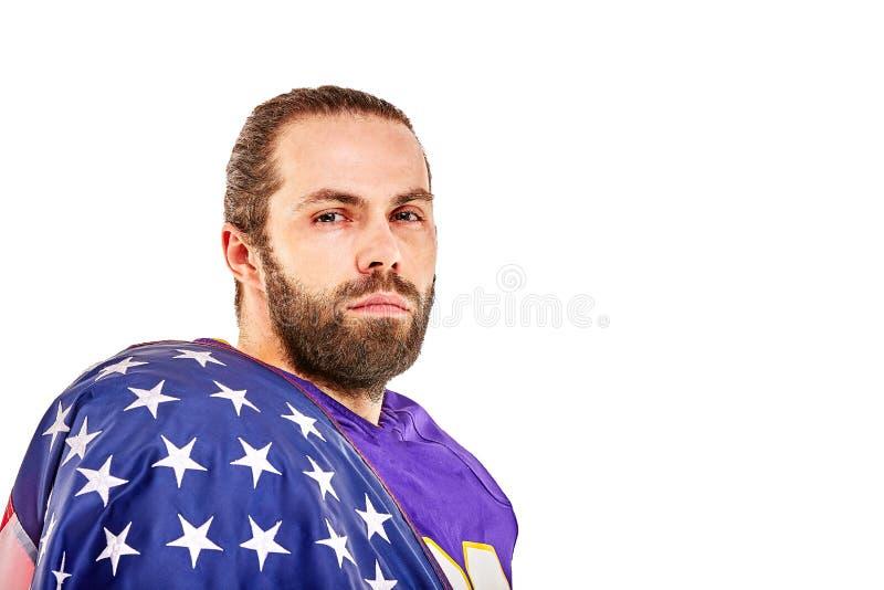 Retrato del primer del jugador de fútbol americano Jugador de fútbol americano con una bandera americana en sus manos Concepto imágenes de archivo libres de regalías
