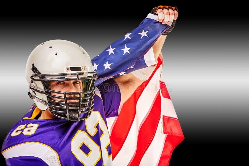 Retrato del primer del jugador de fútbol americano Jugador de fútbol americano con una bandera americana en sus manos Concepto imagen de archivo libre de regalías