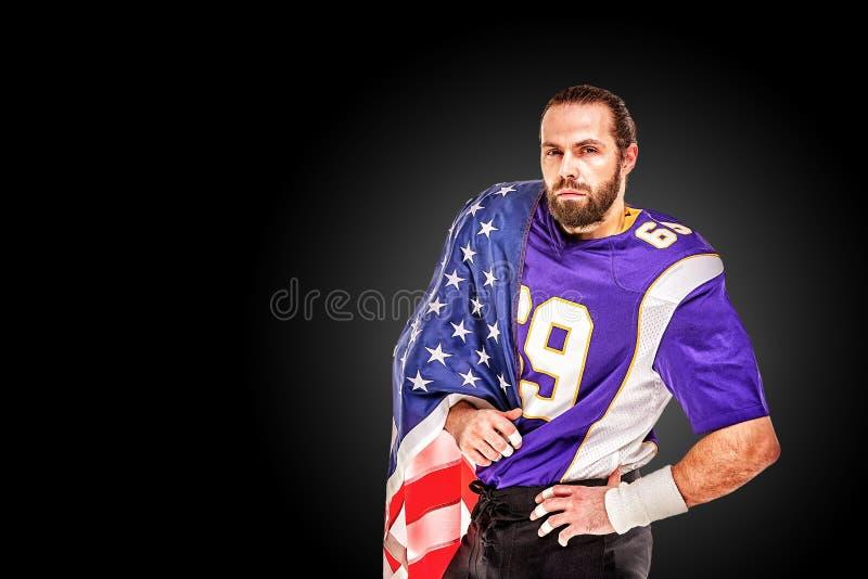 Retrato del primer del jugador de fútbol americano Jugador de fútbol americano con una bandera americana en sus manos Concepto foto de archivo libre de regalías
