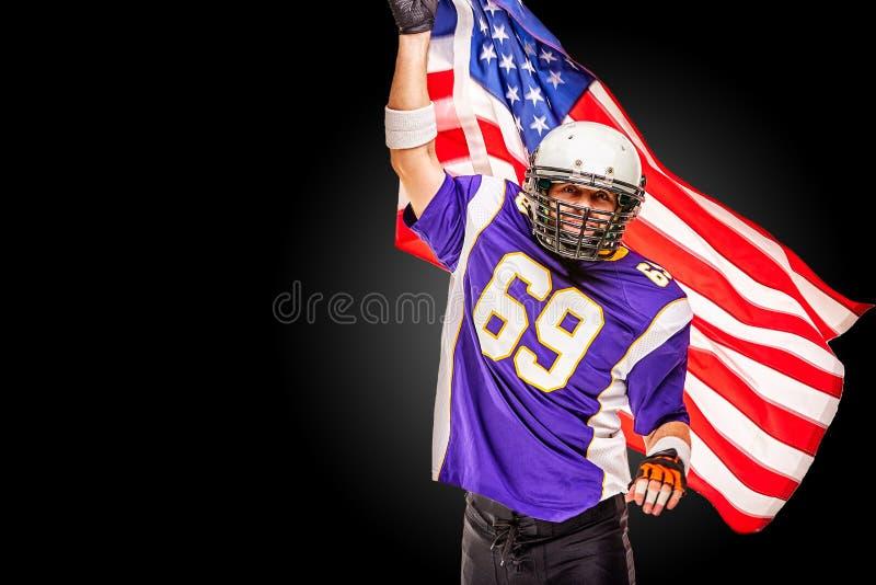 Retrato del primer del jugador de fútbol americano Jugador de fútbol americano con una bandera americana en sus manos Concepto fotos de archivo libres de regalías