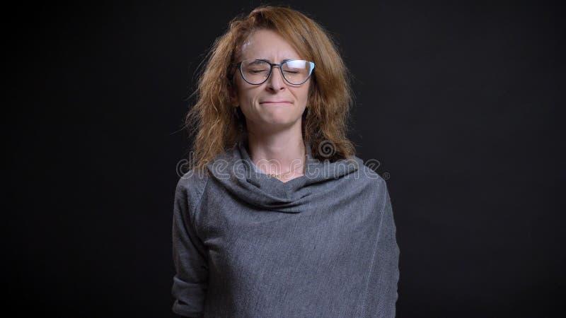 Retrato del primer del pelirrojo extravagante de mediana edad femenino en los vidrios que están deprimidos y tristes delante de l imagen de archivo