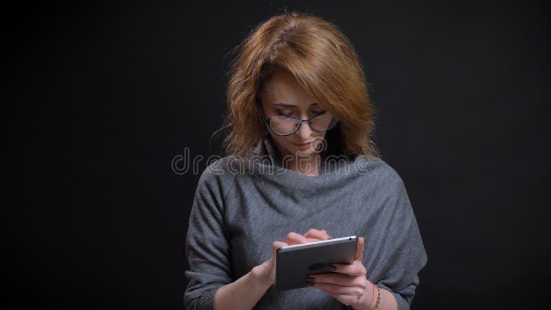 Retrato del primer del pelirrojo extravagante de mediana edad femenino en los vidrios que mandan un SMS en la tableta delante de  imagenes de archivo