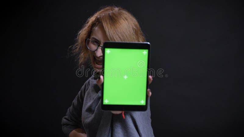 Retrato del primer del pelirrojo extravagante de mediana edad femenino en vidrios usando la tableta y mostrar la pantalla verde a imagen de archivo
