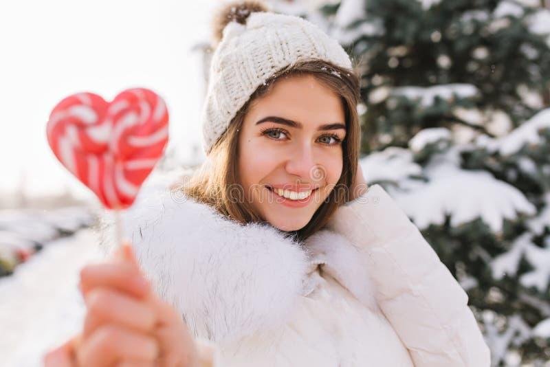 Retrato del primer que sorprende a la muchacha sonriente alegre por mañana soleada del invierno con el lollypop rosado en la call imagen de archivo
