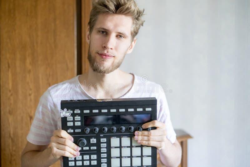 Retrato del productor barbudo joven del sonido del hombre que sostiene el controlador midi y los auriculares f fotos de archivo