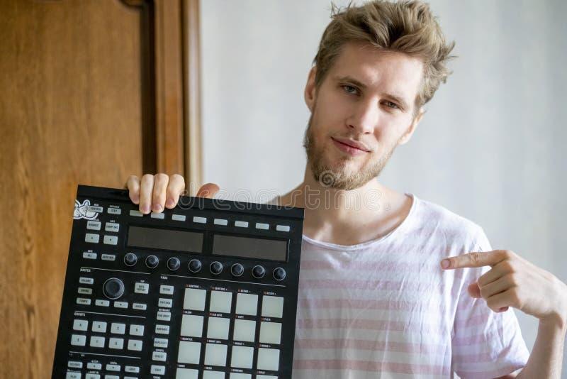 Retrato del productor barbudo joven del sonido del hombre que sostiene el controlador midi y los auriculares f fotografía de archivo