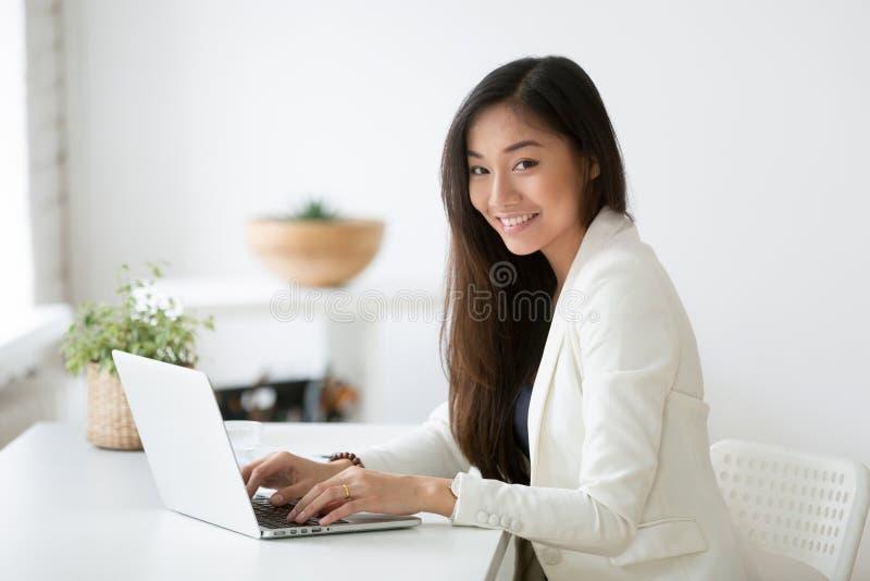 Retrato del profesional asiático femenino que plantea la sonrisa en la cámara foto de archivo