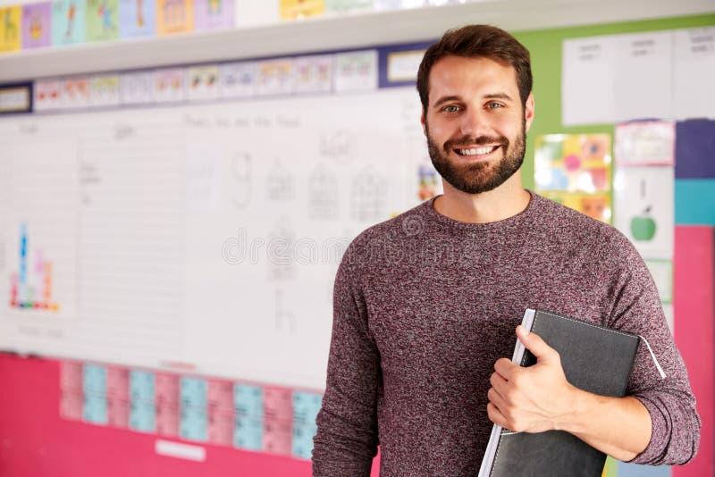 Retrato del profesor de escuela elemental de sexo masculino Standing In Classroom fotografía de archivo