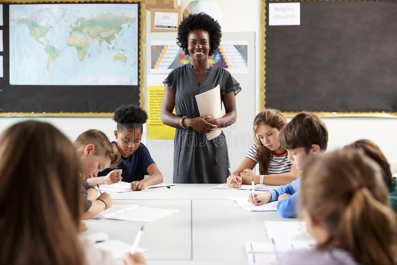 Retrato del profesor de secundaria de sexo femenino Standing By Table con los estudiantes en la lección imágenes de archivo libres de regalías