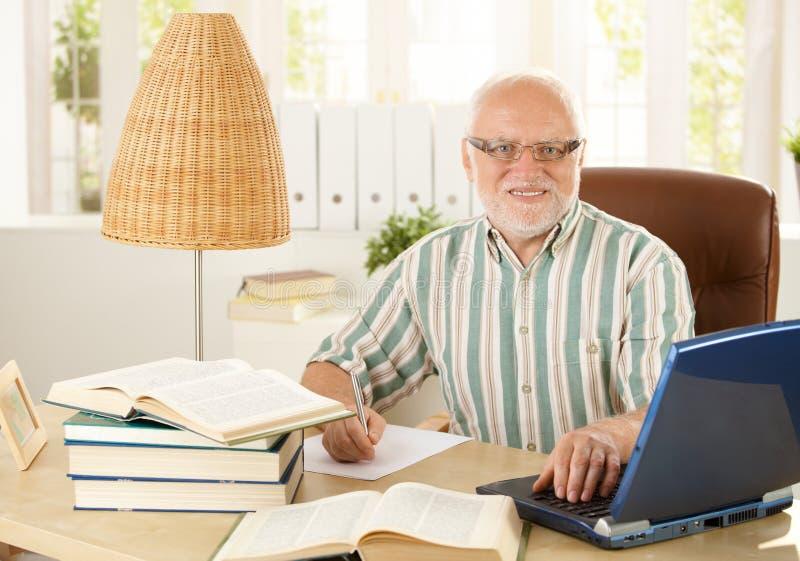 Retrato del profesor mayor que se sienta en el escritorio imagen de archivo libre de regalías