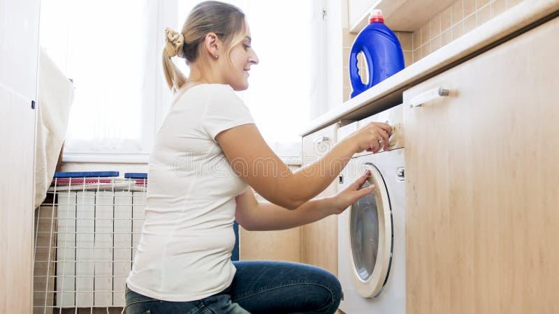 Retrato del programa joven sonriente del ajuste del ama de casa sobre la lavadora fotografía de archivo