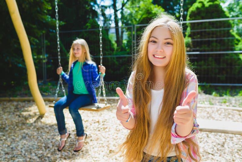 Retrato del pulgar feliz y sonriente de la demostración del niño para arriba en el parque En el fondo la otra muchacha que monta  imagen de archivo