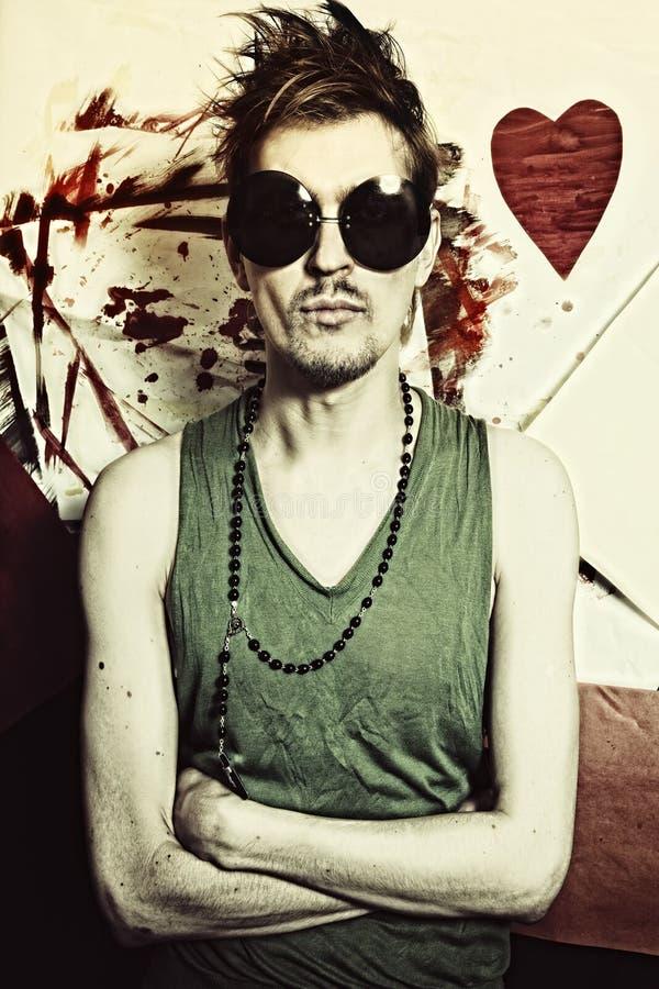 Retrato del punky joven en gafas de sol redondas foto de archivo