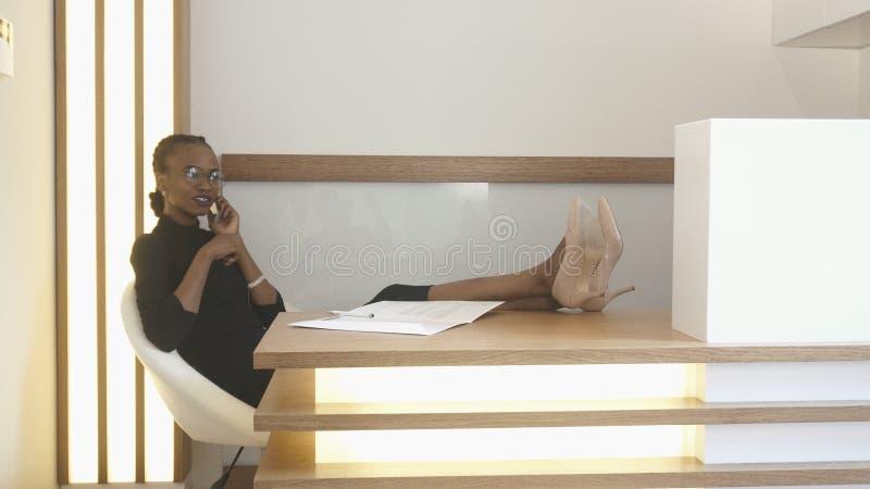Retrato del recepcionista africano hermoso feliz con maquillaje natural y de lentes que hablan activamente vía el móvil foto de archivo