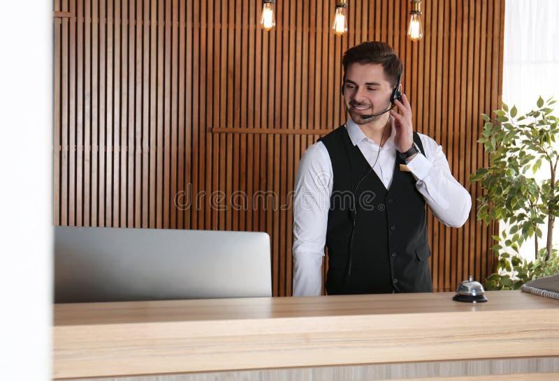 Retrato del recepcionista con las auriculares en el escritorio imagen de archivo libre de regalías