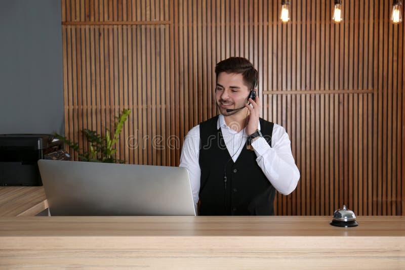 Retrato del recepcionista con las auriculares en el escritorio imágenes de archivo libres de regalías
