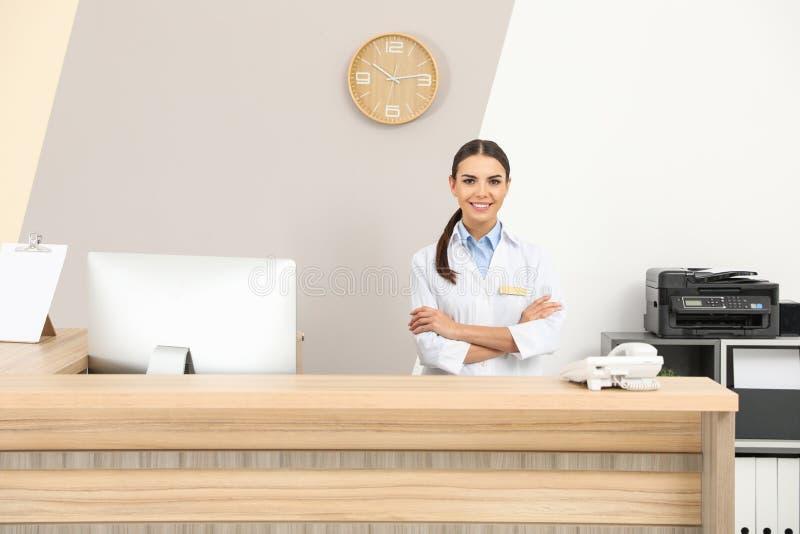 Retrato del recepcionista en el escritorio en clínica imagen de archivo libre de regalías
