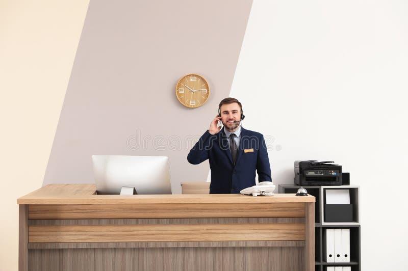 Retrato del recepcionista que trabaja en el escritorio en hotel fotografía de archivo