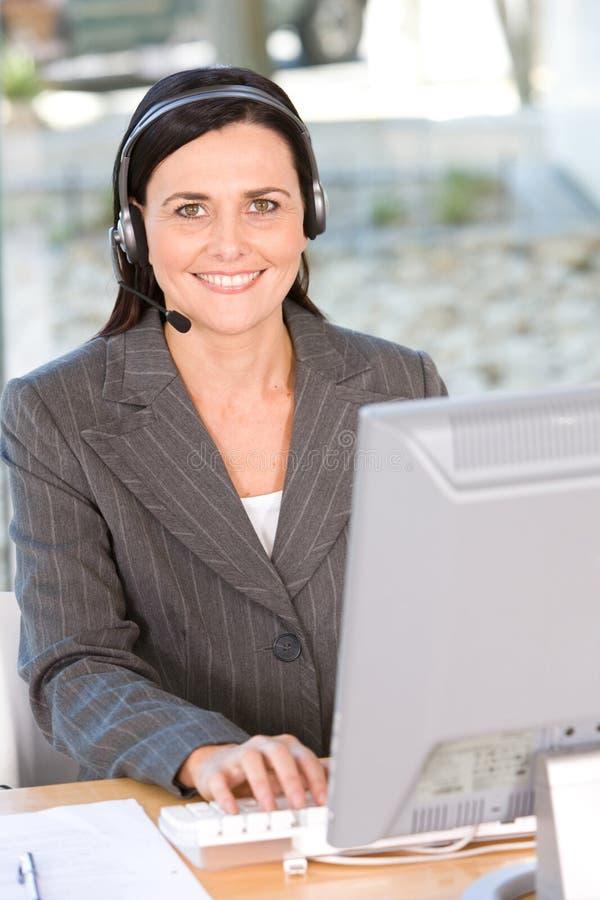 Retrato del receptor de cabeza que desgasta de la mujer usando el ordenador foto de archivo libre de regalías