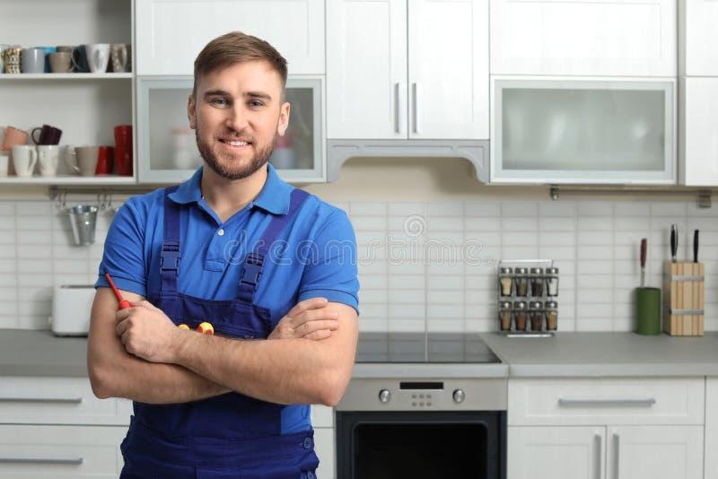 Retrato del reparador con las herramientas cerca del horno en cocina foto de archivo libre de regalías