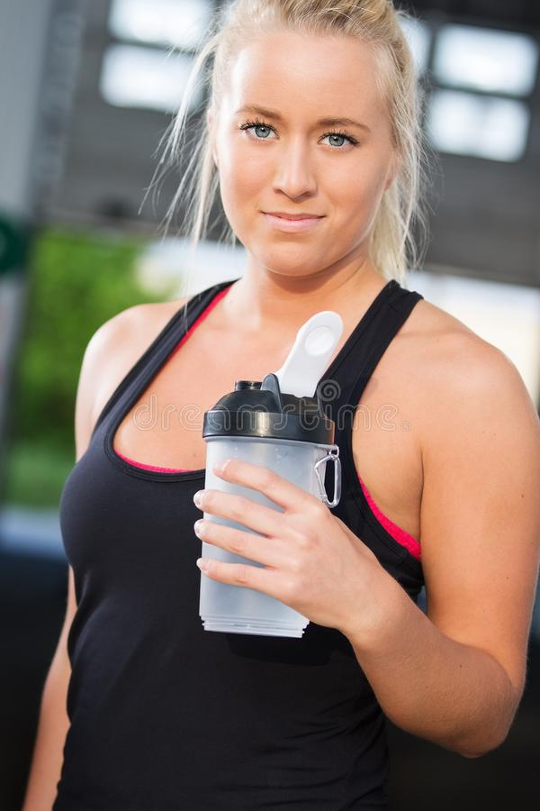 Retrato del resto de la mujer y agua potable en el gimnasio de la aptitud fotos de archivo