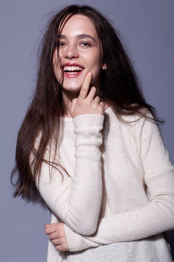 Retrato del retrato moreno joven feliz sonriente de la mujer en blanco imagen de archivo libre de regalías