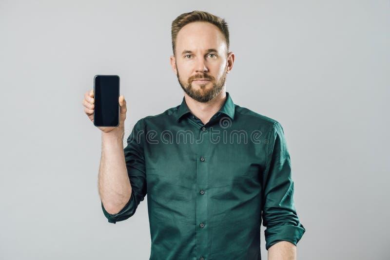 Retrato del smartphone atractivo alegre de la demostración del hombre fotos de archivo
