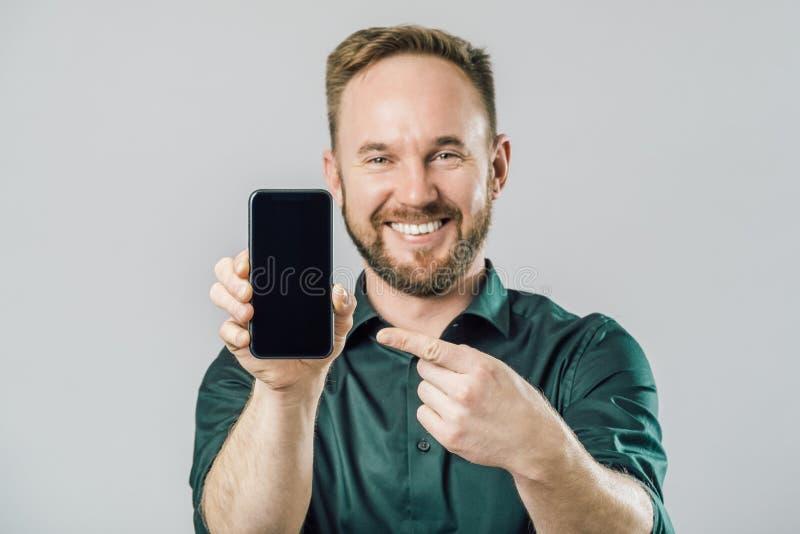 Retrato del smartphone atractivo alegre de la demostración del hombre fotografía de archivo
