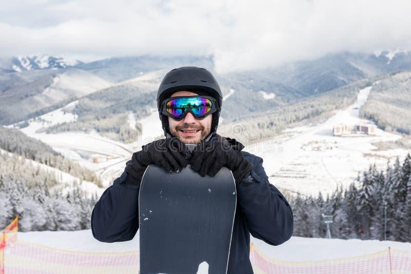 Retrato del snowboarder alegre en la parte superior de la cuesta del esquí en la estación de esquí imagenes de archivo