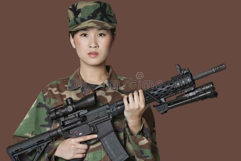 Retrato del soldado hermoso de los E.E.U.U. Marine Corps de los jóvenes con el rifle de asalto M4 sobre fondo marrón imagenes de archivo