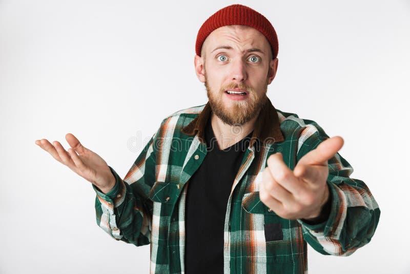Retrato del sombrero desconcertado del individuo barbudo y de la camisa de tela escocesa que llevan que se preguntan, mientras qu fotos de archivo