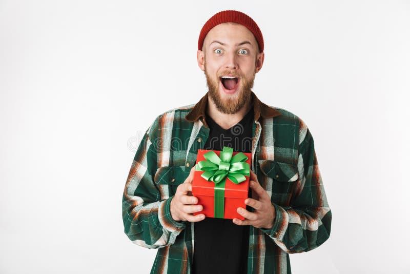 Retrato del sombrero del individuo barbudo hermoso y de la camisa de tela escocesa que llevan que sostienen la actual caja, mient imagen de archivo