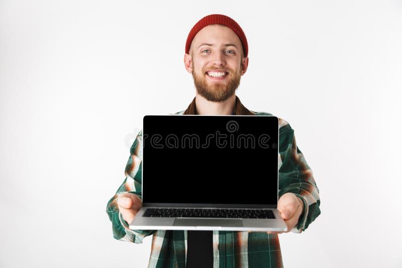 Retrato del sombrero del individuo caucásico y de la camisa de tela escocesa que llevan que sostienen el ordenador portátil de pl fotografía de archivo