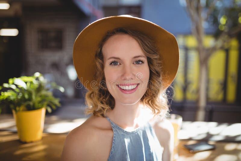 Retrato del sombrero que lleva sonriente de la mujer hermosa el día soleado imagen de archivo