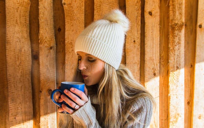 Retrato del soplo de la mujer joven de la belleza a la taza azul de té en el casquillo blanco imagenes de archivo