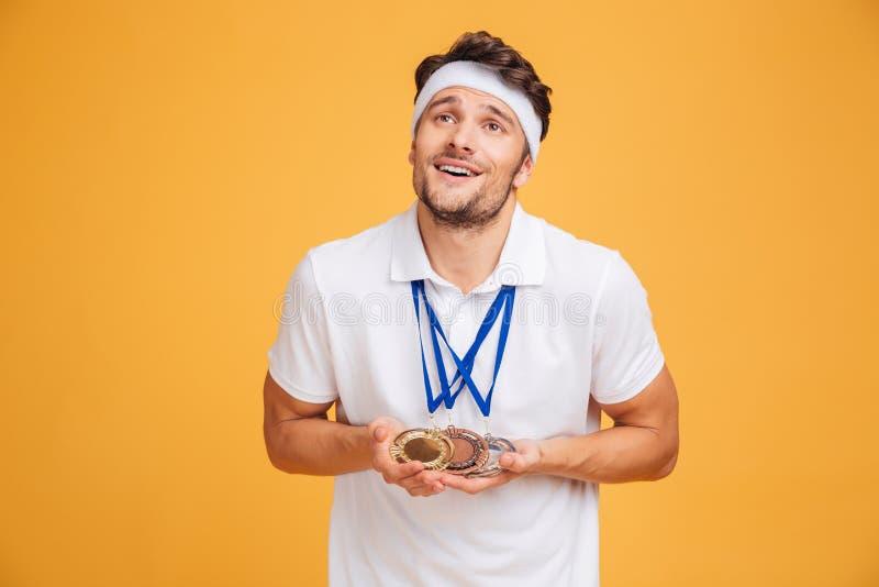 Retrato del spotrsman joven sonriente con tres medallas fotografía de archivo