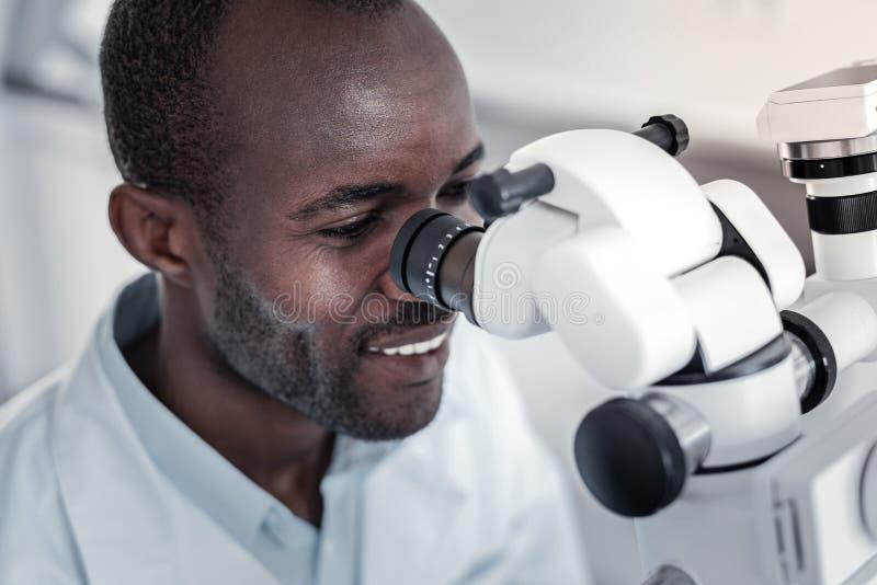 Retrato del stomatologist de piel morena que tratando al paciente imagen de archivo